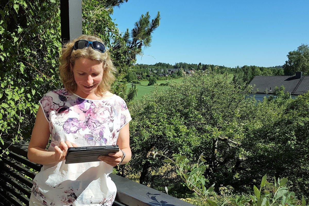 Tove sjekker den nye versjonen av gårdskart på verandaen
